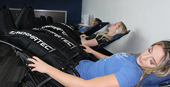 Three customers relaxing back with Normatec Compression Sleeves