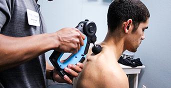 US Cryo technician applying theragun to lower neck of customer